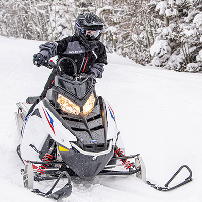 POLARIS<sup>&reg;</sup> RMK EVO Snowmobile - Enjoy this snowmobile which is designed with compact ergonomics to accommodate a wide range of riders.  Features include optimized seating position, easy to reach throttle, suspension engineered for a stable and effortless ride, adjustable-stance Independent Front Suspension, and speed electronically limited to 50 mph.